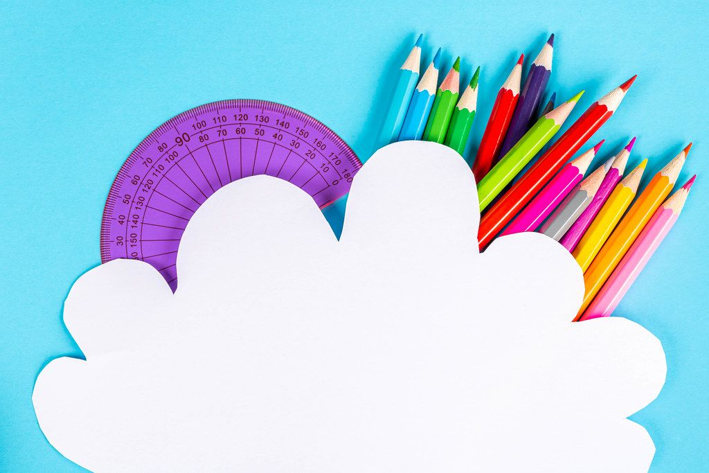 White paper cloud on a blue background with colored pencils and protractor