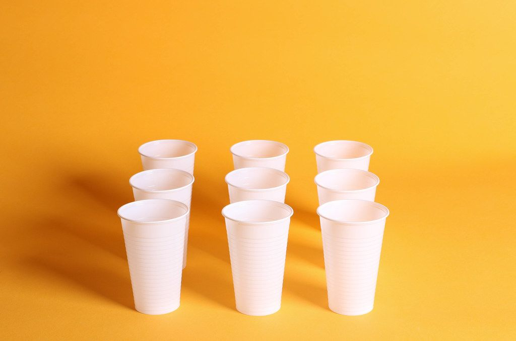 White plastic cups on a orange background