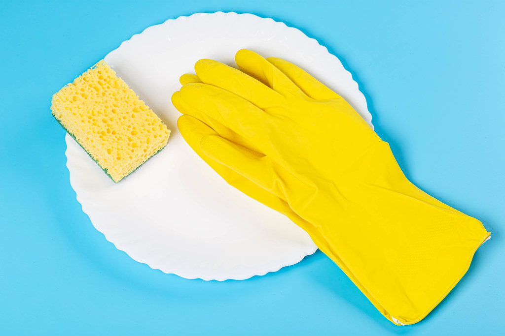 White plate, rubber gloves and a sponge on a blue background