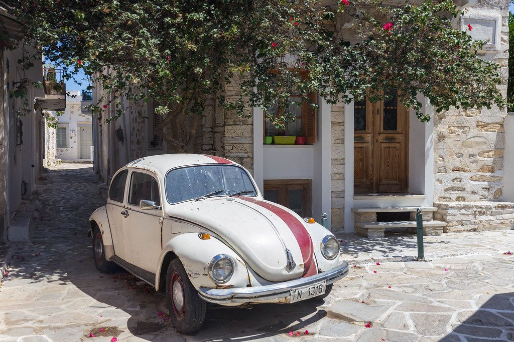 White-red Volkswagen Beetle classic car in an alley of the village of Chalki on Naxos, Cyclades, Greece