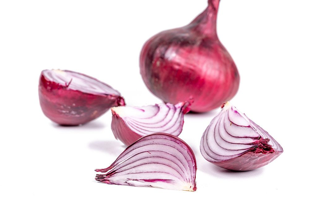 Whole and pieces of purple onion on a white background