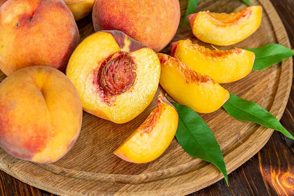 Whole and sliced fresh peaches on a wooden background with leaves