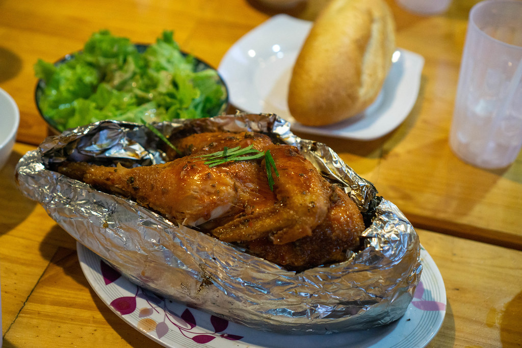 Whole Grilled Chicken in Aluminium Foil on a Wooden Table with Mixed Green Salad and Banh Mi Baguette as Side Dishes