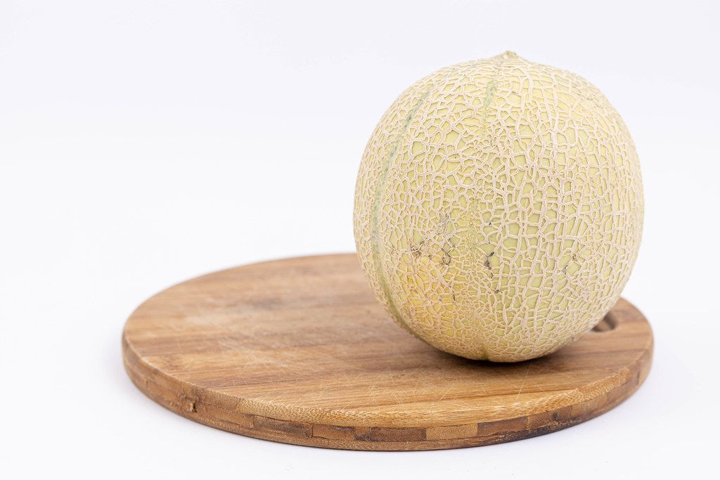 Whole Melon on the wooden board isolated above white background
