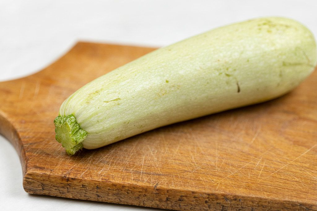 Whole Raw Zucchini on the wooden cutting board