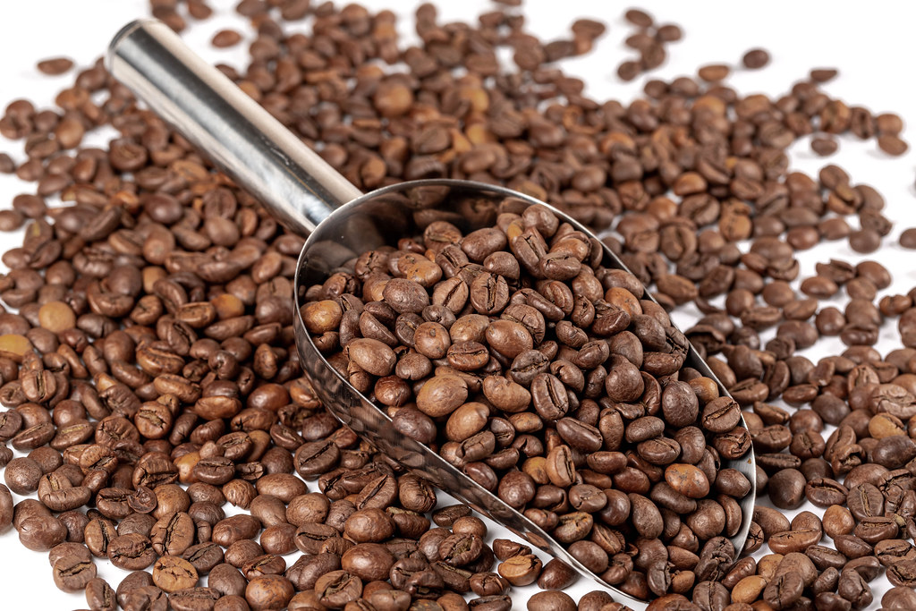 Whole roasted coffee beans background with metal scoop
