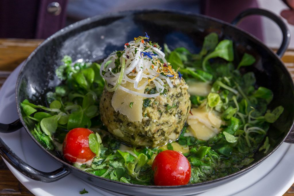 Wild garlic Knödel (Alpine dumpling) in a pan with salad and tomatoes at Dauerstoa Alm in Alpbach