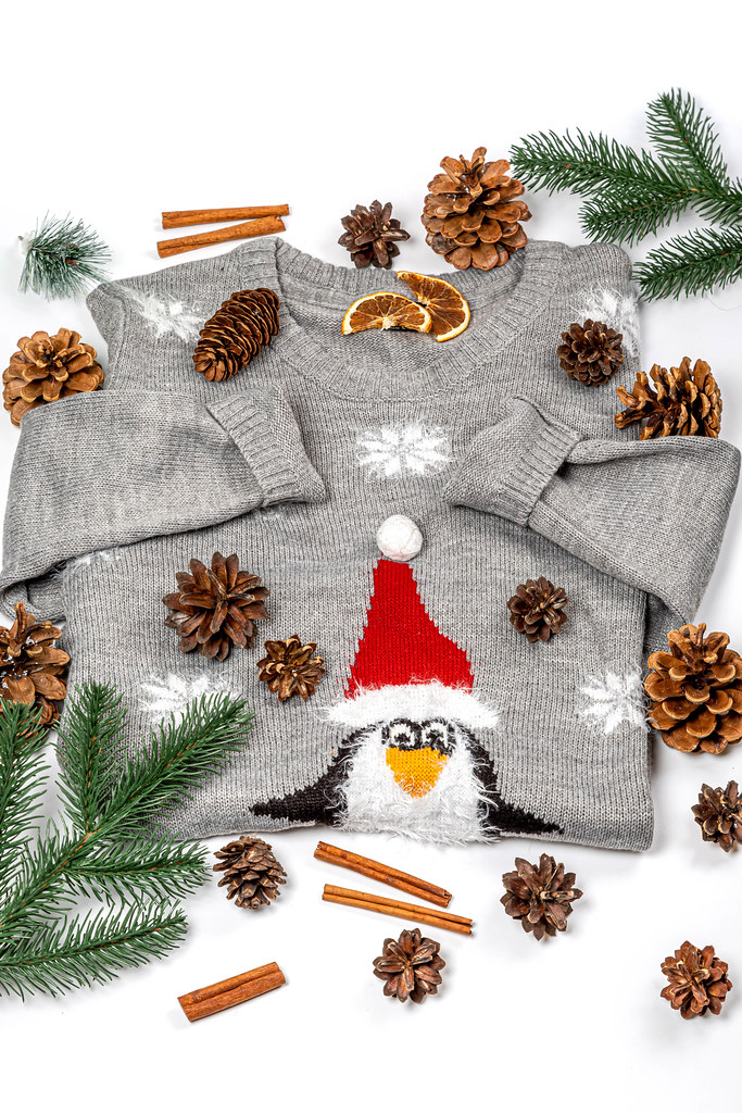 Winter background with sweater, christmas tree branches and pine cones on white