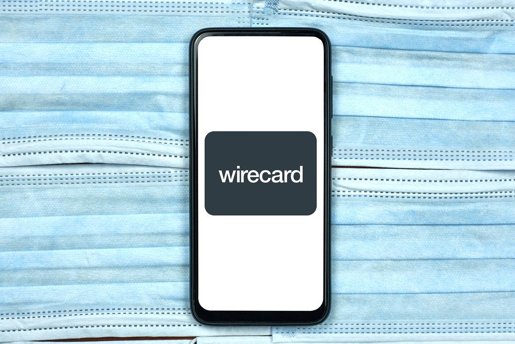 Wirecard logo on smartphone screen over the face masks. Global company during coronavirus crisis