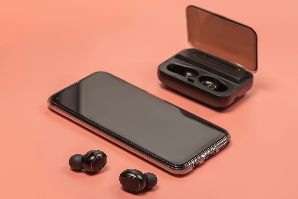 Wireless headphones and smartphone on pink background