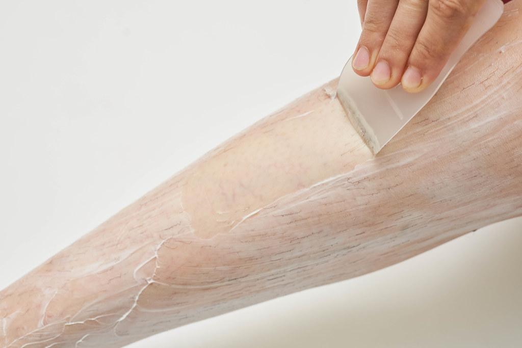 Woman epilating legs depilatory cream and remove it with a spatula