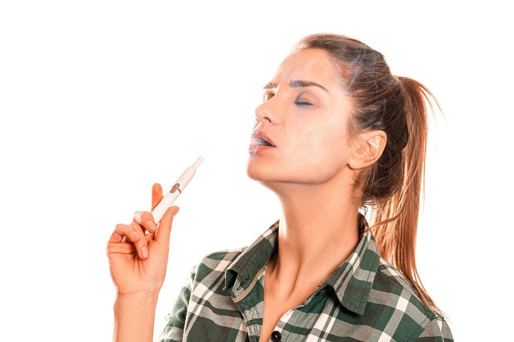 Woman exhales smoke while smoking hybrid cigarette