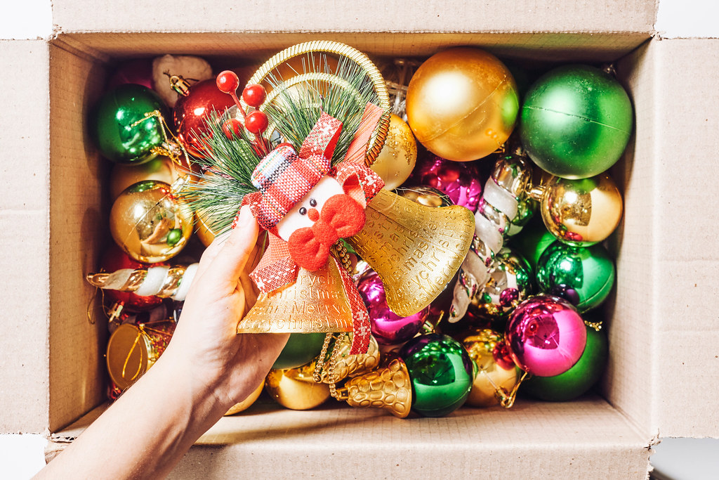 Woman hand takes out Christmas decorations from box