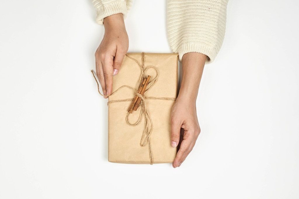 Woman holds handmade Xmas gift wrapped with craft paper