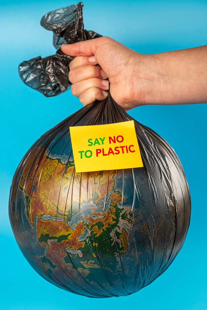 Woman holds in hands garbage bag and planet earth with text sticker - say no to plastic. The concept of plastic pollution