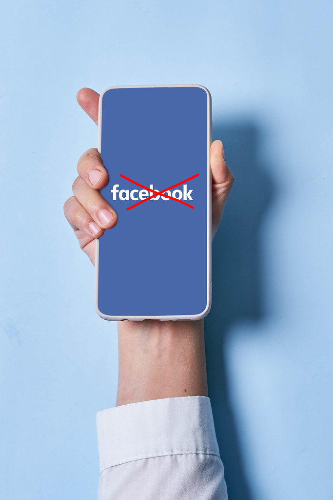 Woman holds smartphone with Facebook logo crossed with red lines