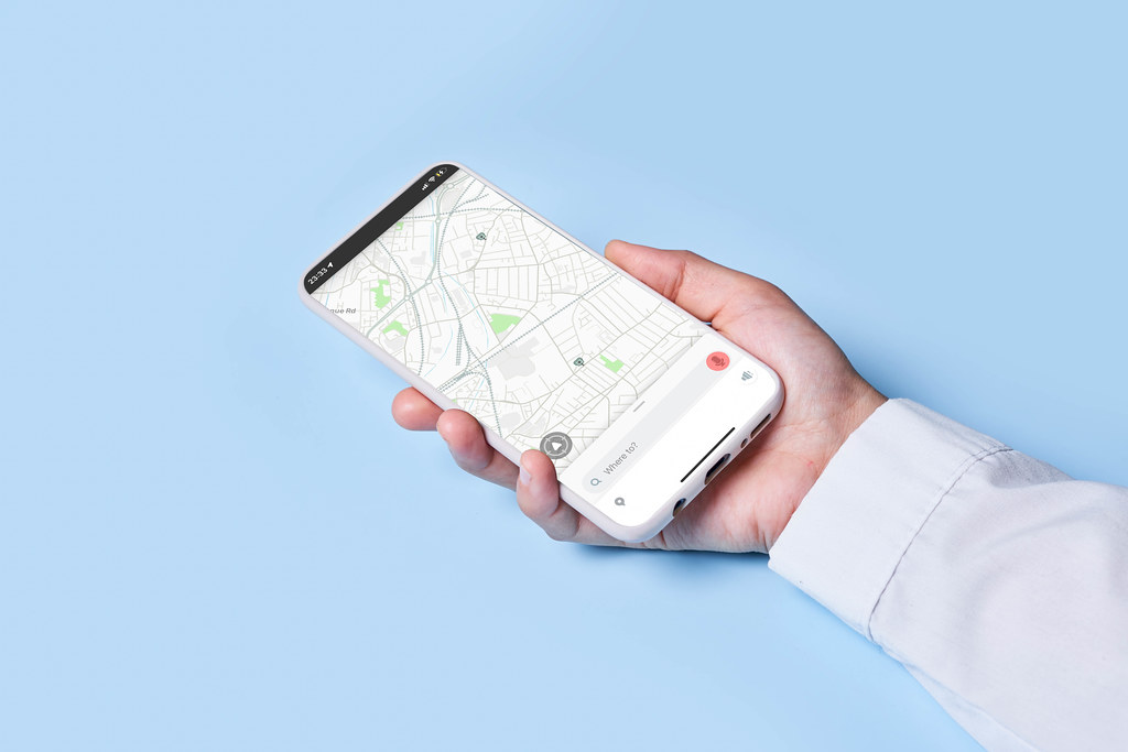 Woman holds smartphone with location map