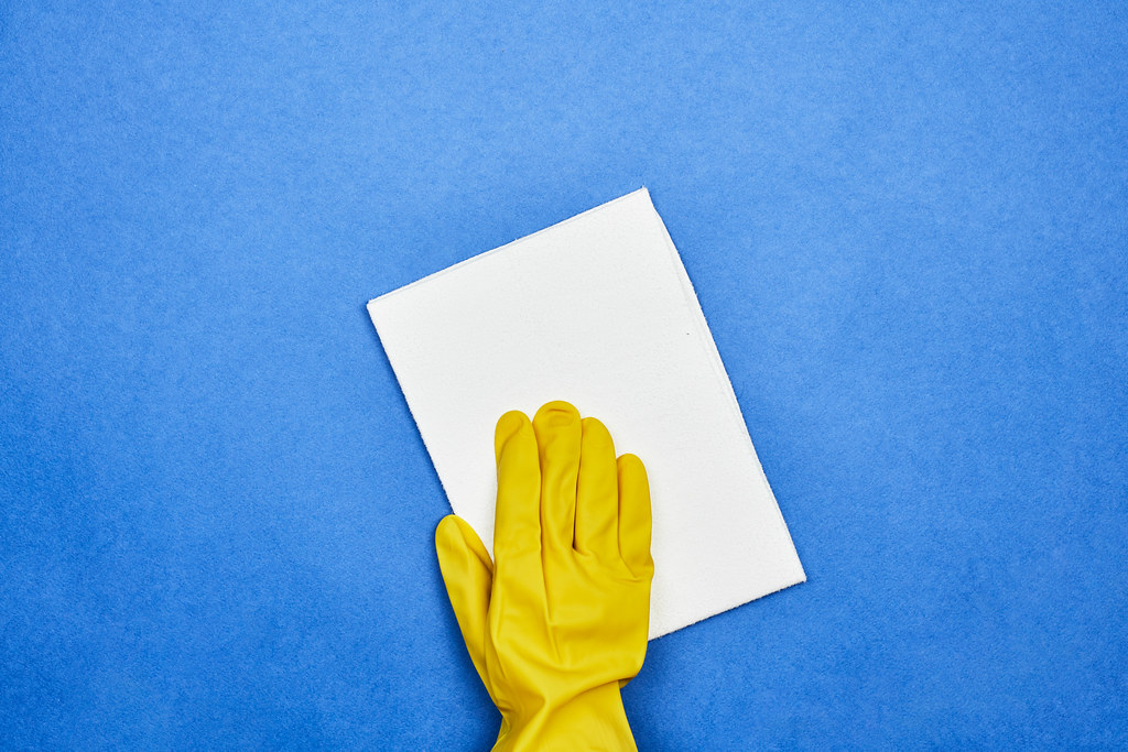 Woman in rubber gloves cleaning blue surface with a wipe