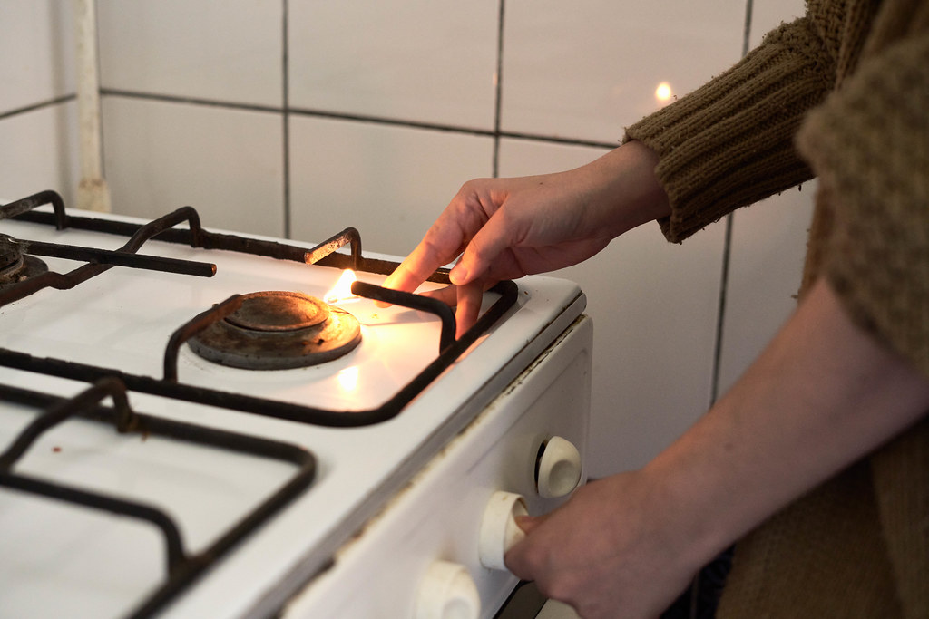 Woman lighting gas stove with match