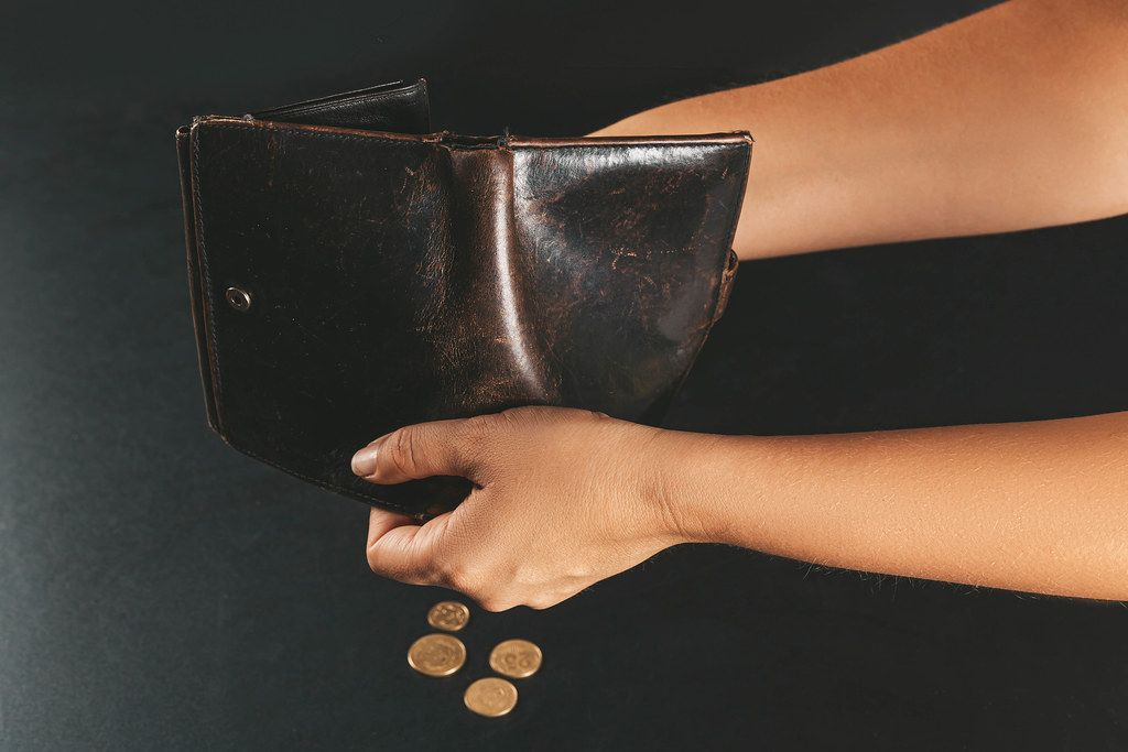 Woman pouring coins from wallet, concept of financial constraints, poverty