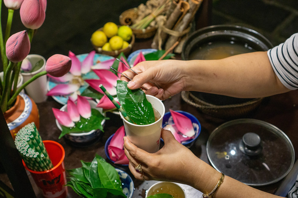 Woman preparing Traditional Herbal Tea with Lotus Flowers, Leaves, Lime and Lemongrass in a Paper Cup with Paper Straw in Hoi An, Vietnam
