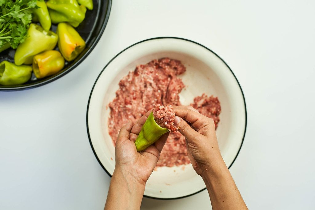 Woman putting minced meat into the green bell pepper