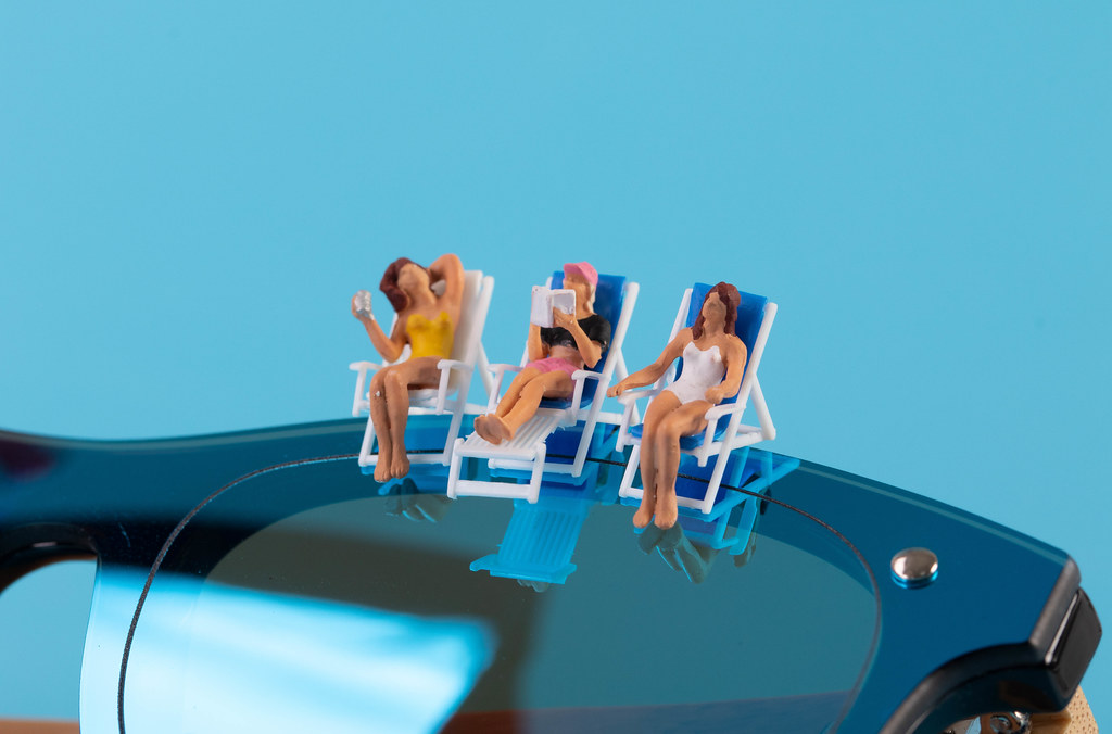 Woman sitting in deck chairs on top of the sunglasses