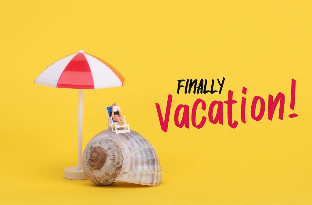 Woman sitting on top of the sea shell and Finally Vacation text