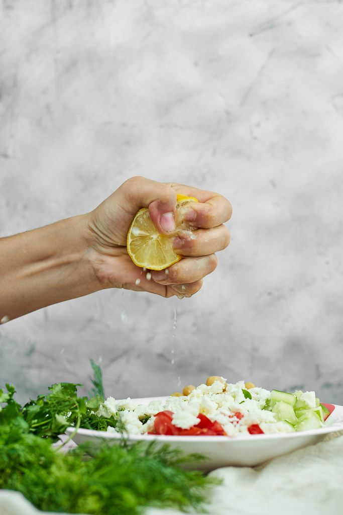 Woman squeezing lemon in a plate with a healthy vegetable salad