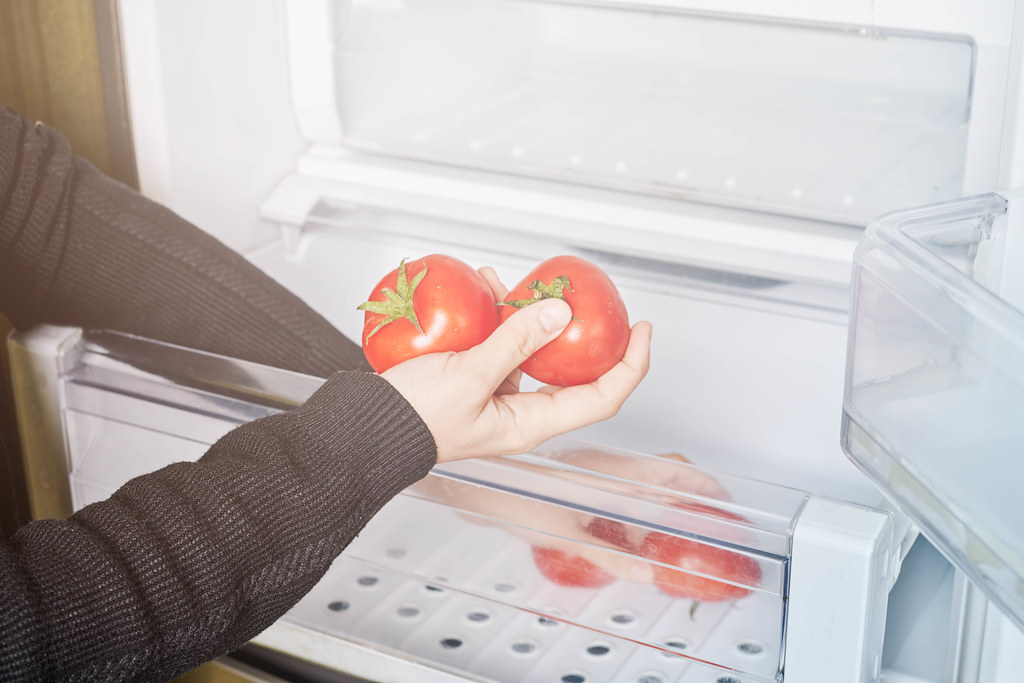 Woman taking fresh tomatoes from the salad crisper drawers of refrigerator