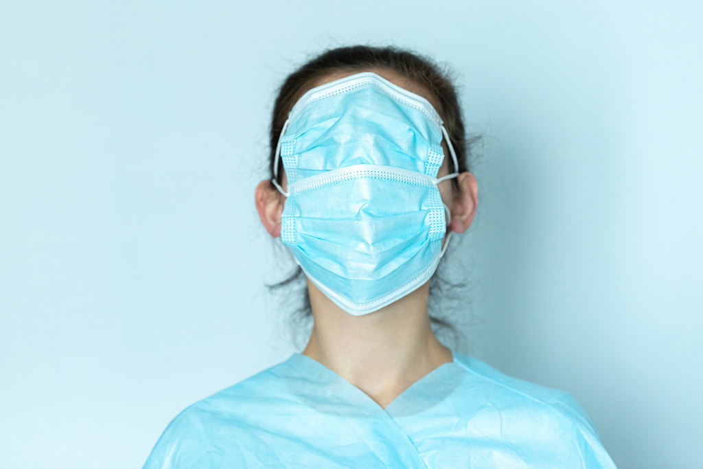 Woman wearing a face mask over his eyes, concept fake news, blue background