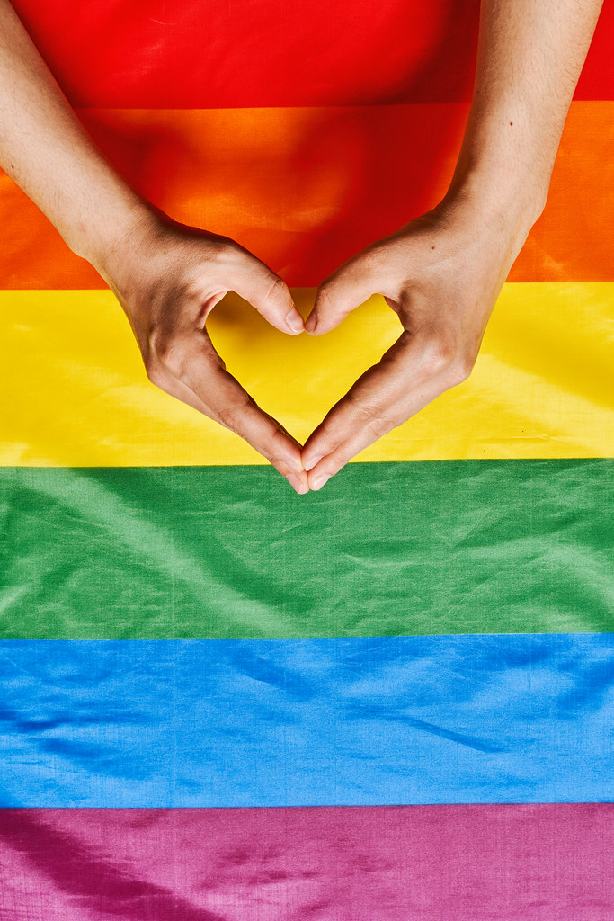 Womans hands making heart shape over the lgbtq rainbow flag background