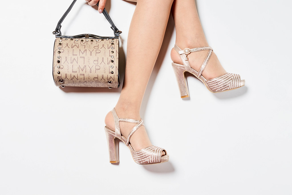 Woman's legs wearing high heel shoes and holding a handbag