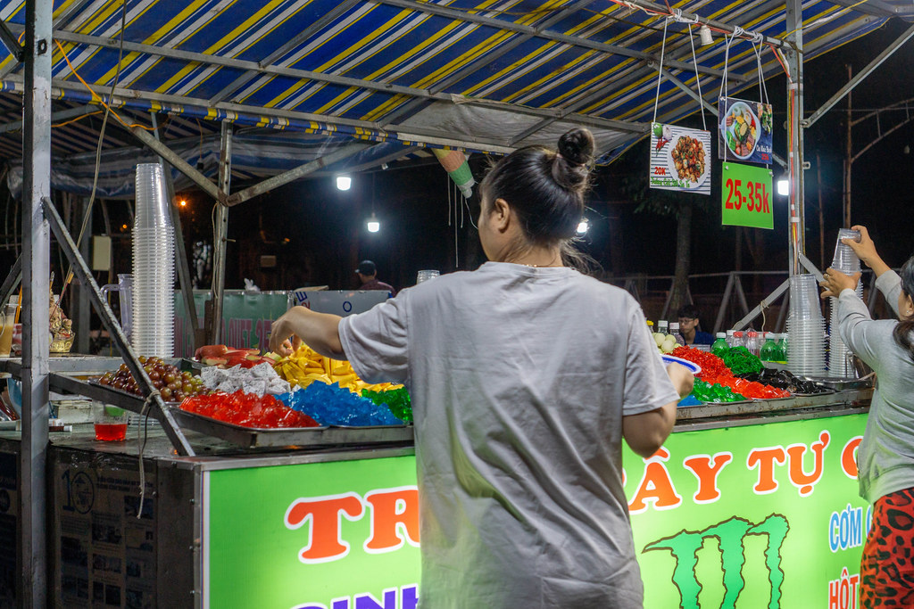 Women picking different Fruits and Jelly to make their own Fruit Bowl at a Street Food Vendor at a Night Market in Can Tho, Vietnam