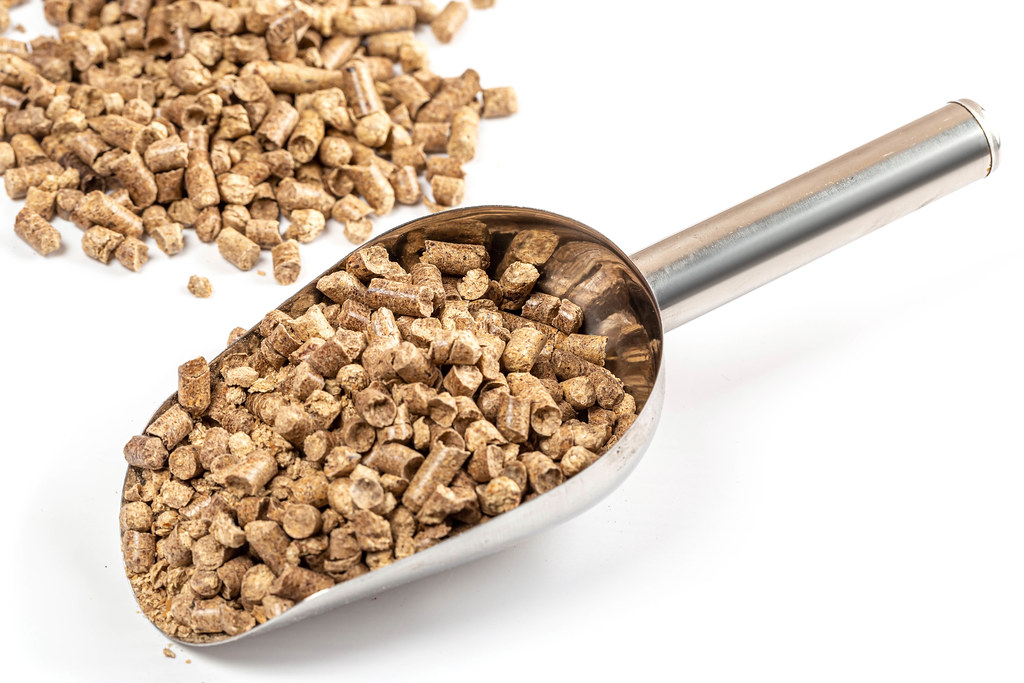 Wood pellets filler for pets toilets with scoop on white