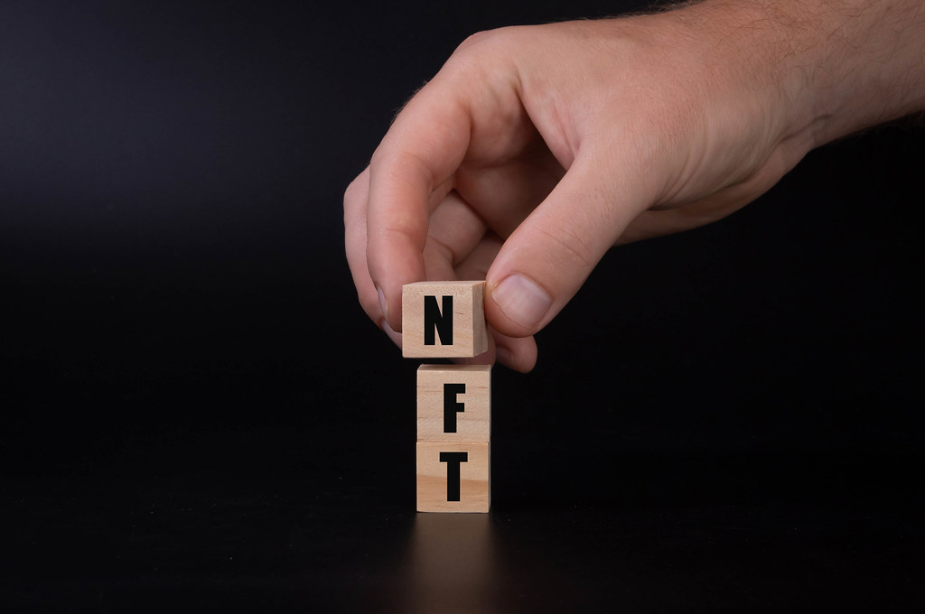 Wooden blocks with NFT text and hand on black background