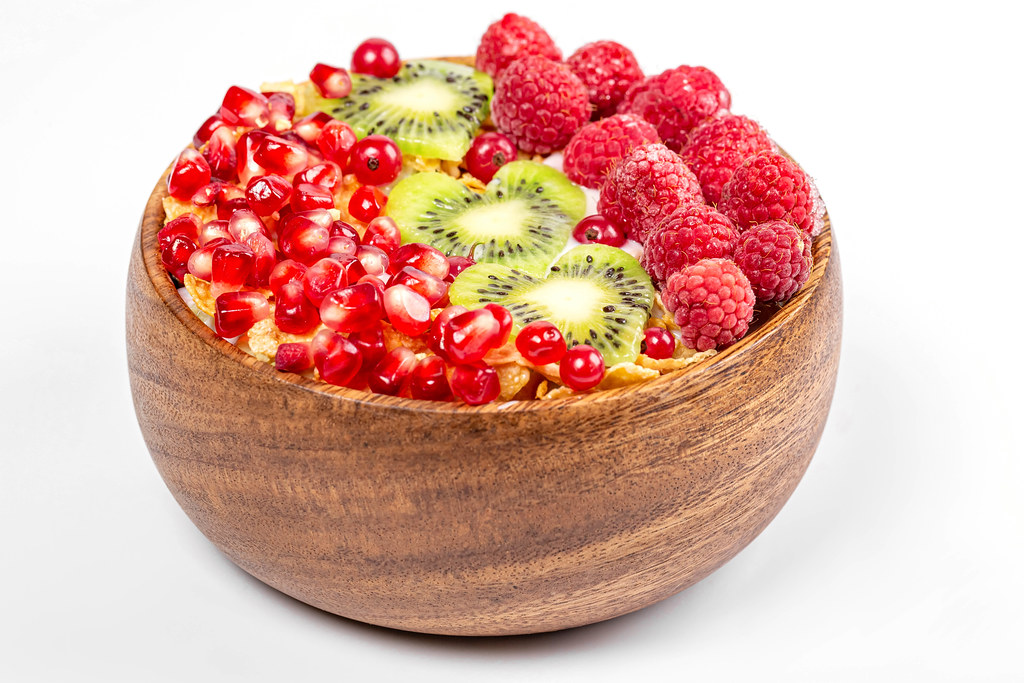 Wooden bowl with cornflakes, yogurt, pomegranate, kiwi and raspberries