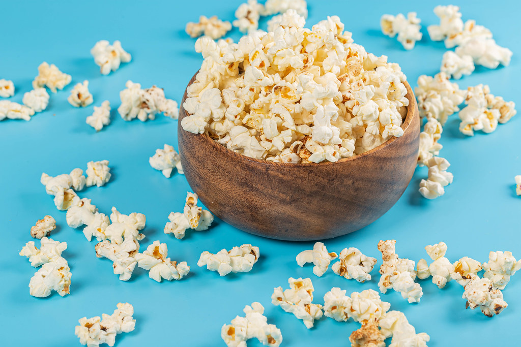 Wooden bowl with popcorn on a blue background
