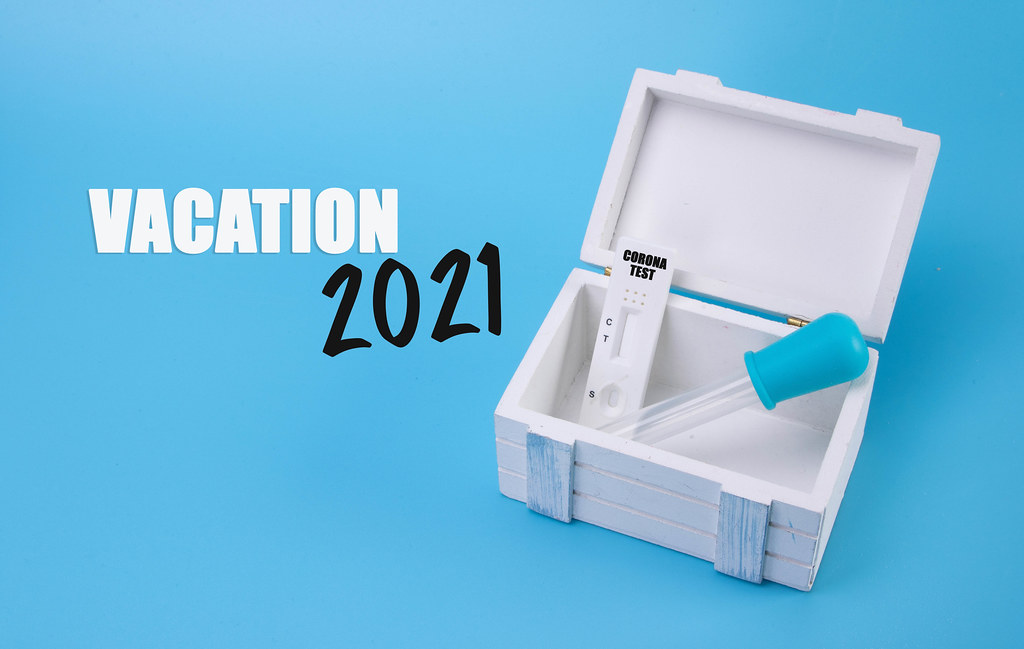 Wooden box with Coronavirus test and Vacation 2021 text on blue background