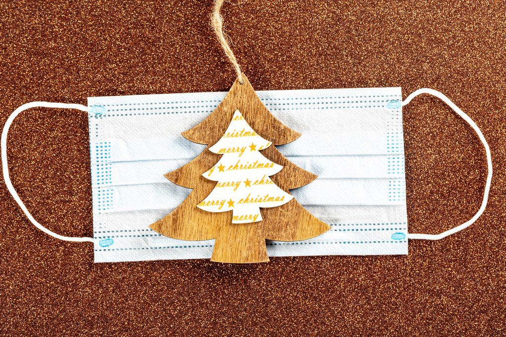 Wooden Christmas tree and medical mask on shiny brown background
