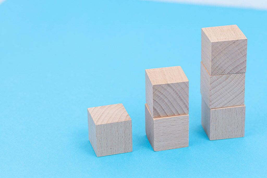 Wooden Cubes stairs with copy space above blue background