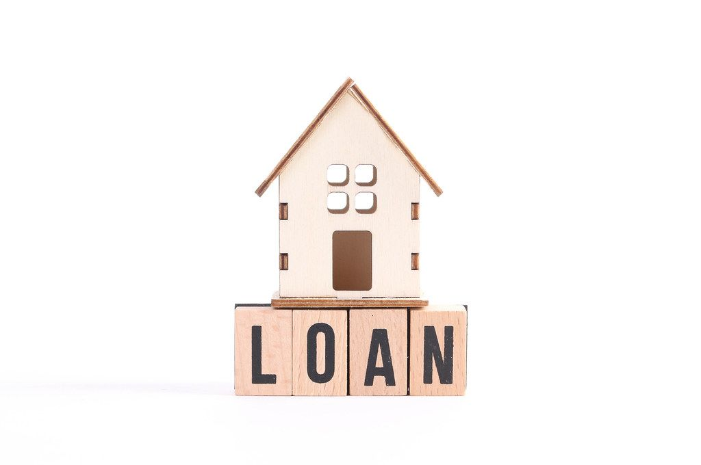 Wooden house and the word Loan on white background