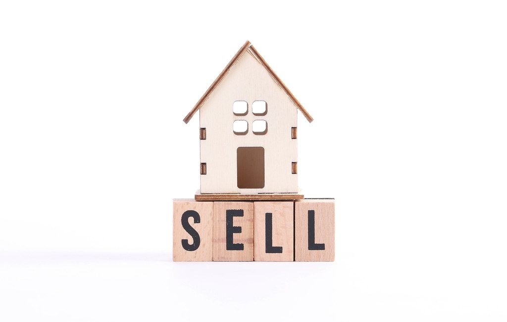Wooden house and the word Sell on white background