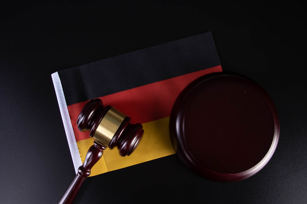 Wooden judge gavel and flag of Germany