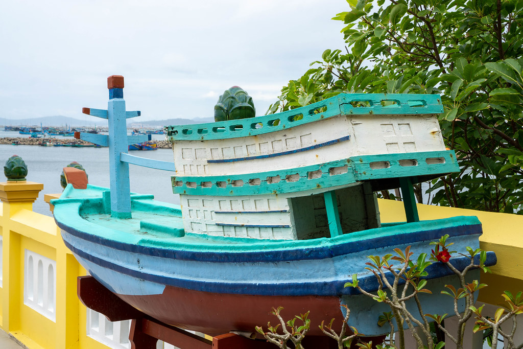 Wooden Miniature Fishing Boat at Dinh Cau Shrine with Mountains and Harbour in the Background in Phu Quoc, Vietnam