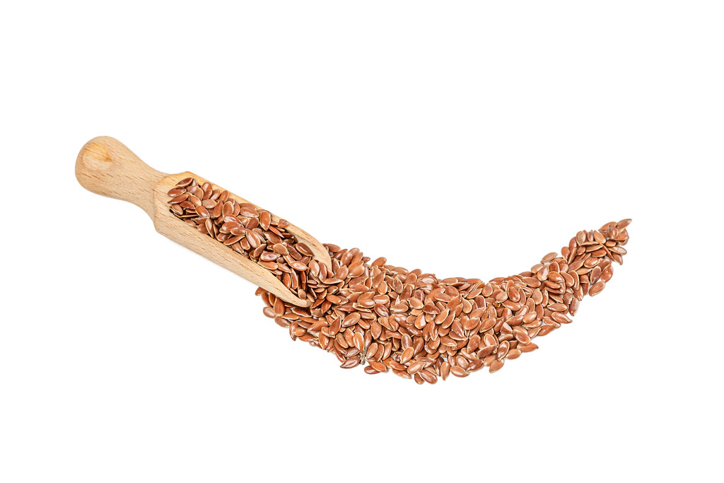 Wooden scoop with flax seeds on white