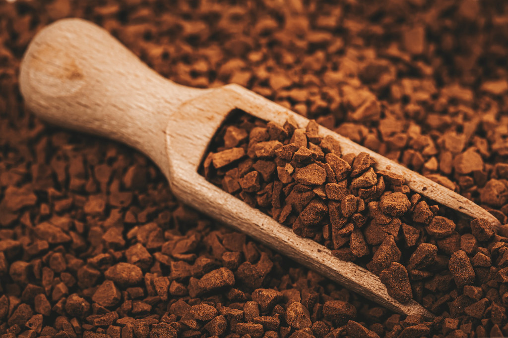 Wooden scoop with granules of instant coffee close-up