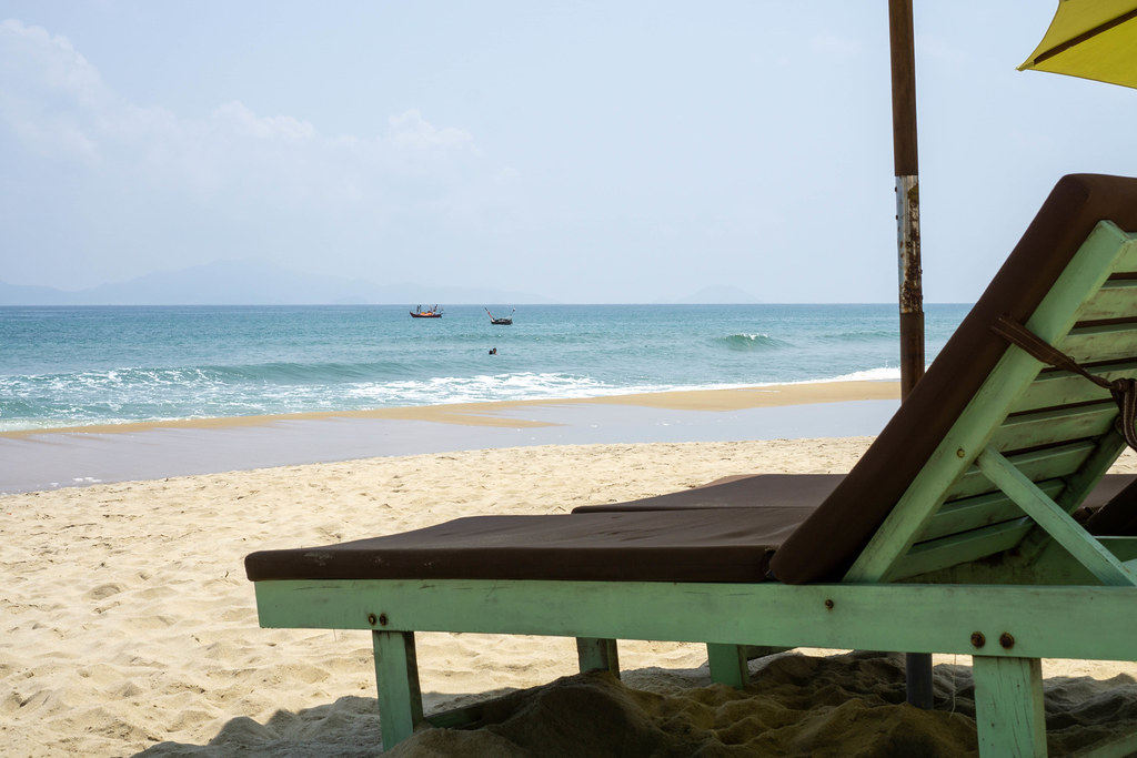 Wooden Sun Bed with Cushion and Sun Umbrella at An Bang Beach with View of Fishing Boats in Hoi An, Vietnam
