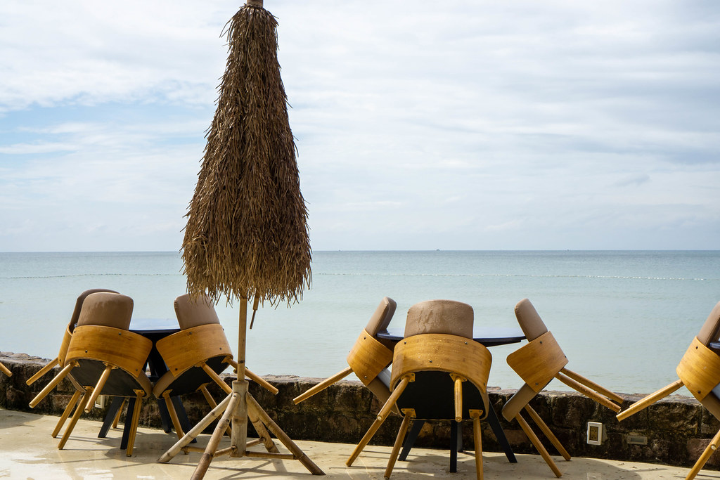 Wooden Tables and Chairs with Bamboo Leaves Sun Umbrella at a Beach Bar on Phu Quoc Island, Vietnam
