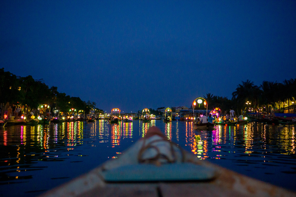 Wooden Tourist Boats with Bright Colorful Lanterns on Thu Bon River with Light reflecting in the Water in Hoi An, Vietnam